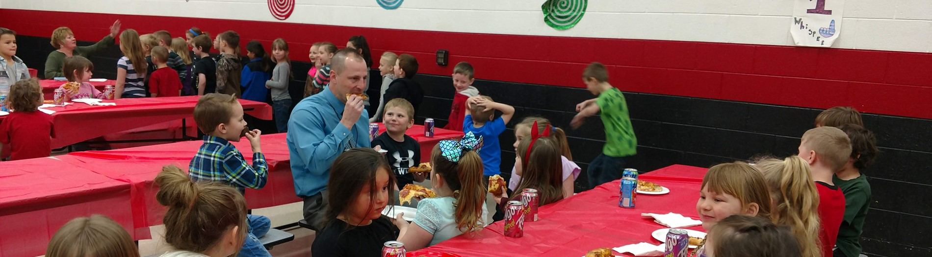 Principal with kids at lunch.